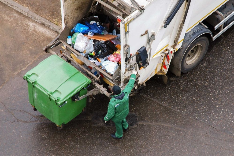 a man operating a garbage truck